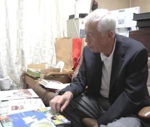 「人形のまるぎん」社長の八木さんとたくさんの節句人形のパンフレット